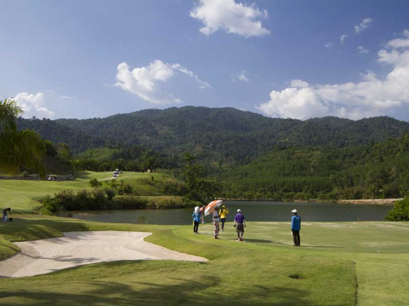 many golfer in front of a mountain