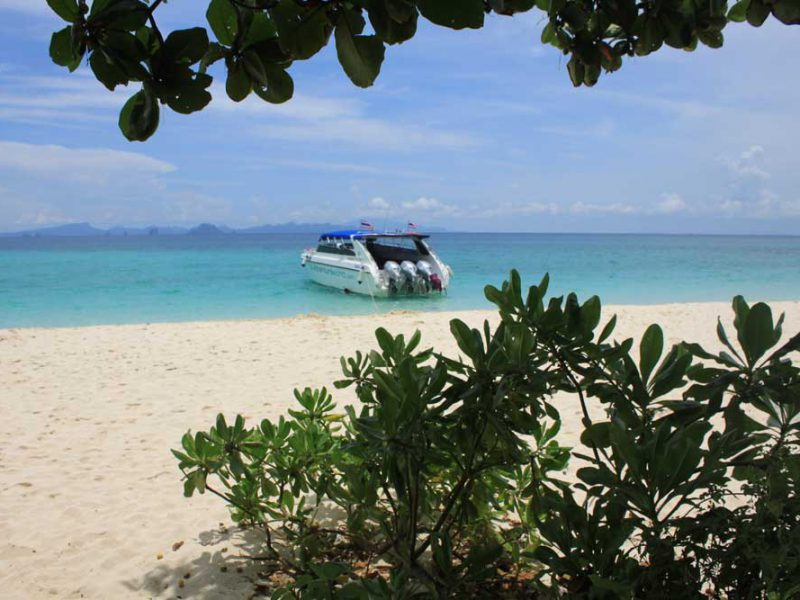 white sandy beach with speedboat